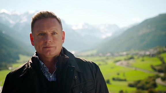 Ein Mann steht im Freiem. Im Hintergrund sind die Alpen zu erkennen