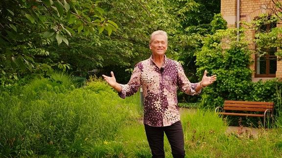 Ein moderator steht in einem grünen Hof.