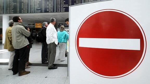 Fluggäste stehen im Flughafen hinter einem Verbotsschild.