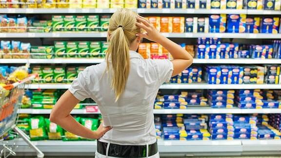 Eine Frau steht vor einem Supermarktregal voller Lebensmittel und hält die Hand an den Kopf.