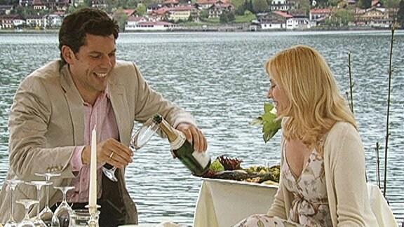Ein junges Ehepaar genießt ein romantisches Frühstück mit Sekt und Kaviar am See