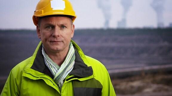 Ein Mann mit Helm und neongrüner Jacke steht am Rande eines Tagebaus und schaut in die Kamera