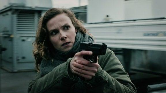 Eine Kommissarin läuft mit gezogener Pistole vorsichtig auf einem Dach