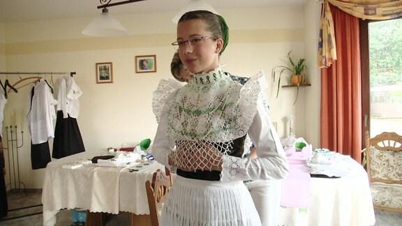 Ein Mädchen ist bei der Anprobe eines traditionellen Sorbichen Kleides