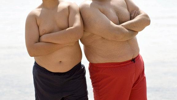 Zwei übergewichtige Männer an einem Strand.