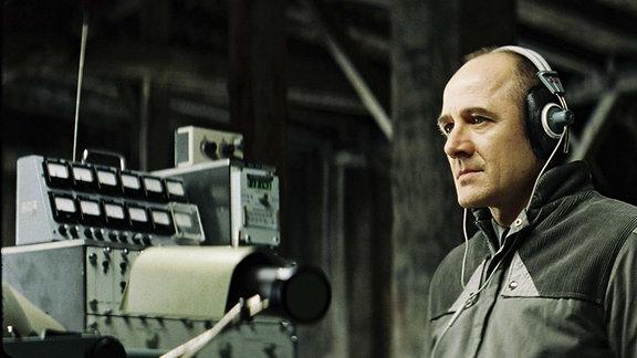 Stasi-Hauptmann Gerd Wiesler (Ulrich Mühe) sitzt in dem Kinofilm (Das Leben der Anderen) auf dem Dachboden eines Hauses und belauscht die Vorgänge in der Wohnung die er beschattet.