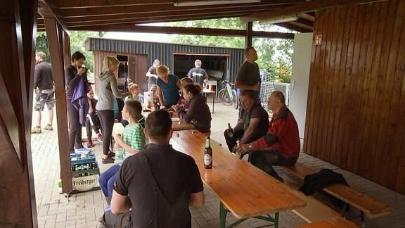 Auf dem Gelände eines Vereins sitzen die dorfbewohner unter einem Dach und feiern gemeinsam