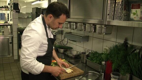 Ein Koch schneidet Gemüse