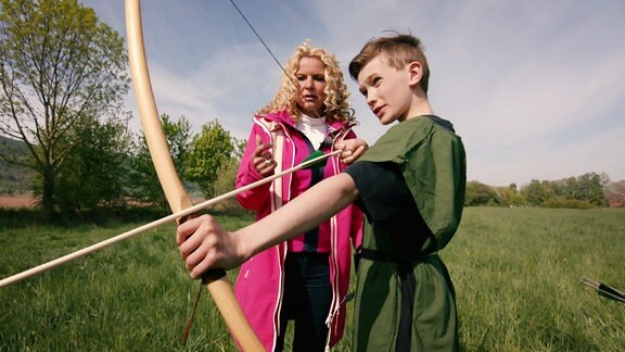 Die Moderatorin lässt sich von einem jungen Knaben das Bogenschiessen erklären