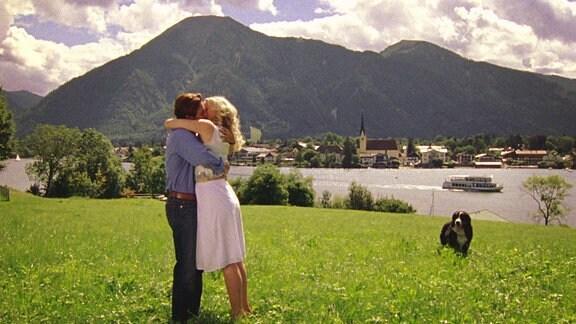 Ein junges paar umarmt und küsst sich leidenschaftlich auf einer grünen Wiese mit Bergen und einem See im Hintergrund