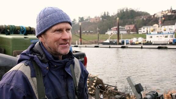 Ein Fischer steht am Rand der Elbe neben seinem Boot