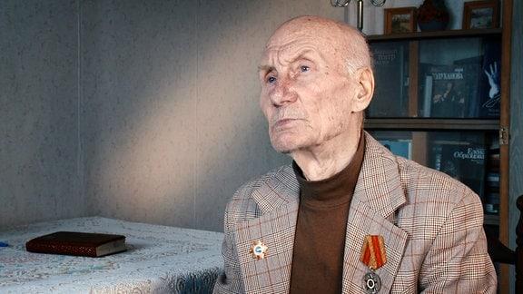Ein alter Mann mit orden an seinem Jacket sitzt in seinem Wohnzimmer und bereichtet