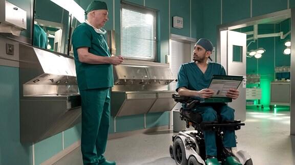 Dr. Roland Heilmann (Thomas Rühmann, li.) ist wenig begeistert, als Dr. Ilay Demir (Tan Caglar, re.) die Vertretung für Dr. Martin Stein übernimmt. Roland ist Ilay etwas zu sehr von sich selbst überzeugt.