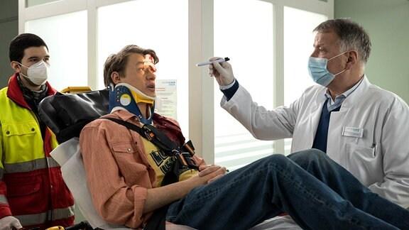 Pepe Kleinert (Vincent Krüger, mi) wird nach einem Autounfall in die Sachsenklinik eingeliefert. Dr. Roland Heilmann (Thomas Rühmann, re.) gegenüber gibt er an, eine Verrückte wäre geradewegs in sein Auto reingefahren. li: Komparse