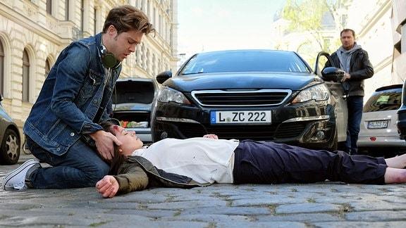 Kris Haas (Jascha Rust, li.) schlendert am Nachmittag durch die Stadt, als er Sanna Lichtenhagen (Diane Willems, liegend) vor ein Auto laufen sieht. Der Fahrer (Frank Haberland, re.) ist schockiert. Kris ist sich sicher, dass dies kein Unfall, sondern Sannas Absicht war.