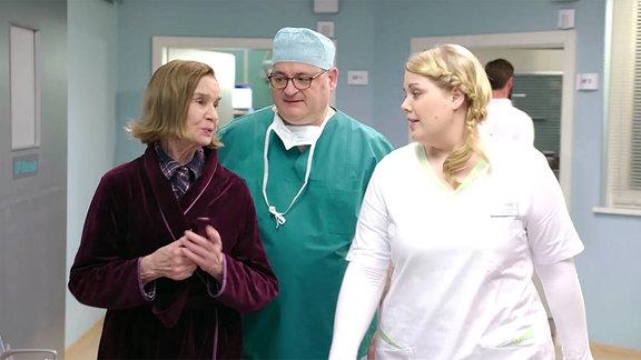 Alte Dame im Bademantel mit Pfleger und Krankenschwester