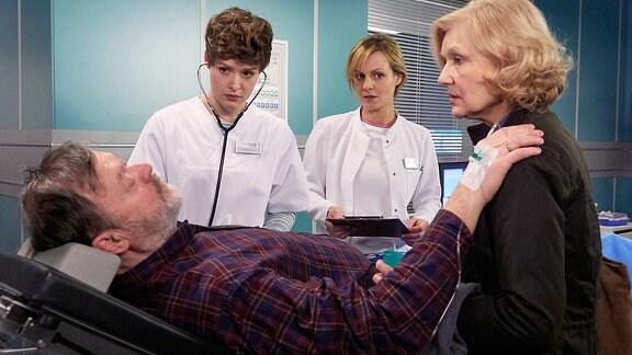 Ein Mann liegt in einem Behandlungszimmer und legt einer blonden Frau seine Hand auf die Schulter. Eine braunhaarige junge Krankenschwester und eine blonde Ärztin stehen daneben