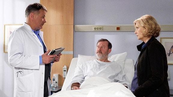Ein Patien liegt im Krankenbett, eine blonde Frau steht neben ihm. Sie hören einem Arzt aufmerksam zu