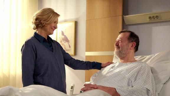 Ein Mann liegt im Krankenbett und schaut lächelnd die blonde Frau an, die neben ihm steht und seine Schulter berührt