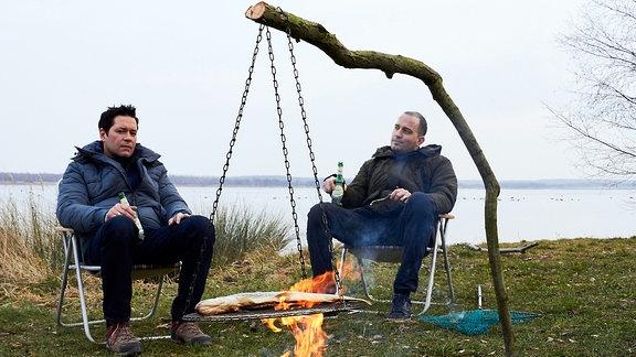 Zwei Angler sitzen an einem See in Campingstühlen am Feuer