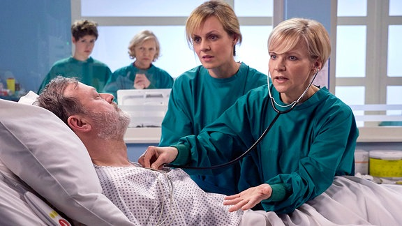 Ein Mann liegt bewusstlos im Krankenbett, zwei Ärztinnen untersuchen ihn