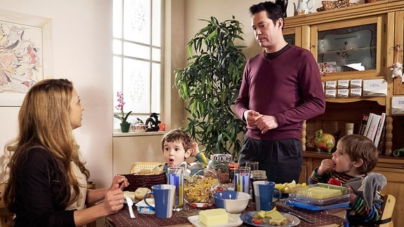 Eine Familie mit zwei kleinen Kindern sitzt am Frühstückstisch