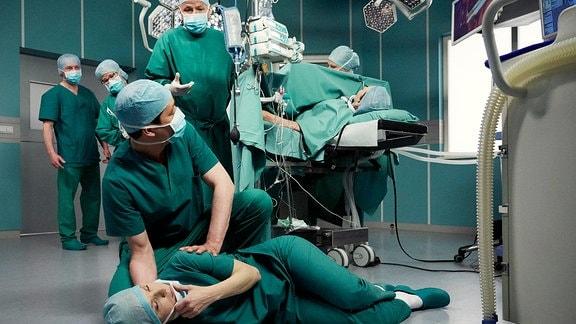 In einem OP Saal ligt die Ärztin Dr. Kathrin Globisch am Boden. Andere Ärzte stehen drumherum.