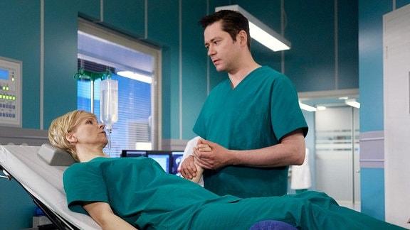 Dr. Kathrin Globisch liegt auf einer Krankenliege. Dr. Philipp Brentano hält ihre Hand.