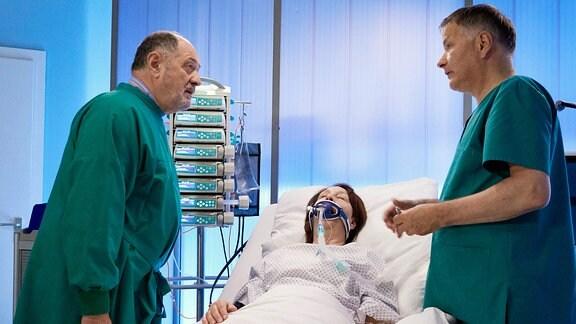 An einem Krankenbett spricht Gustav Thewes (Jürgen Haug, li.) mit Dr. Roland Heilmann (Thomas Rühmann, re.). Im Bett liegt seine Frau Anna (Christine Schmidt-Schaller, mi.) mit einer Sauerstoffmaske.