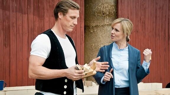 Dr. Lea Peters (Anja Nejarri) spricht mit einem Mann in Zimmermannkluft.