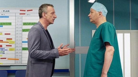 Alexander Weber (Heio von Stetten, li.) spricht mit Roland Dr. Martin Stein in einem Krankenhausflur.
