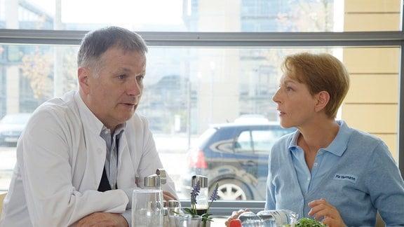 Pia Heilmann (Hendrikje Fitz) möchte von ihrem Mann Dr. Roland Heilmann (Thomas Rühmann) wissen, wie lange er am Nachmittag im OP stehen wird.