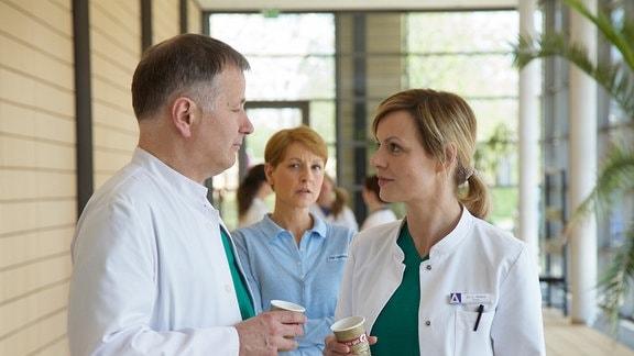 Dr. Roland Heilmann (Thomas Rühmann, li.) und Dr. Lea Peters (Anja Nejarri, re.) haben die anstrengende OP beendet. Respektvoll tauschen sie sich über ihre fachlichen Kompetenzen aus.