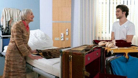 Renate Harnack (Katharina Matz) packt ihren riesigen Übersee-Koffer im Krankenhauszimmer aus. Kris Haas (Jascha Rust) sieht ihr dabei zu