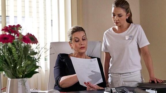 Sarah Marquardt (Alexa Maria Surholt, li.) zeigt Oberschwester Arzu Ritter (Arzu Bazman, re.) in ihrem Büro ein offizielles Schreiben