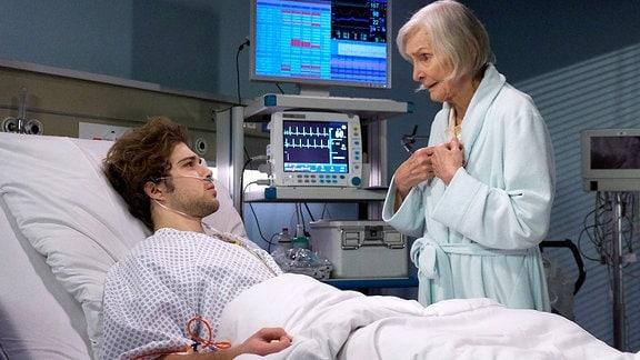 Kris Haas (Jascha Rust) liegt schwer verletzt in einem Krankenbett. Renate Harnacks (Katharina Matz) steht im Bademantel an seinem Bett