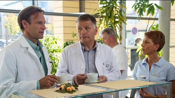 Dr. Stein, Dr. Heilmann und seine Frau Pia in der Cafeteria der Sachsenklinik.