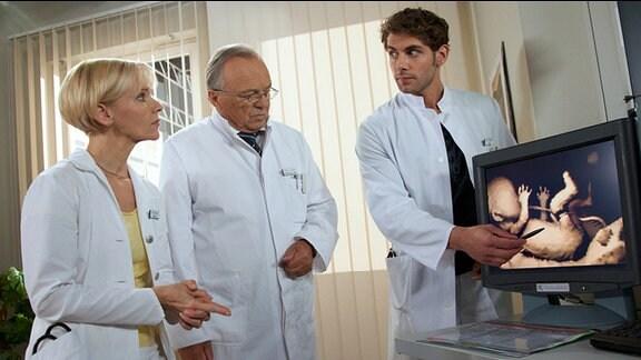 Dr. Niklas Ahrend erklärt Dr. Globisch und Prof. Simoni die bevorstehende Operation Rebeccas.