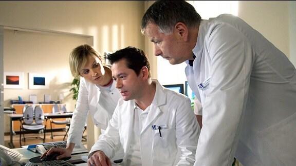 Dr. Philipp Brentano (Thomas Koch, mi.) hält das Leberkarzinom seines Patienten für inoperabel. Dr. Roland Heilmann (Thomas Rühmann, re.) schätzt das genauso ein. Das Risiko einer OP ist unkalkulierbar. Die beiden plädieren dafür, den Patienten auf die Liste für eine Spenderleber zu setzen. Als sich Dr. Lea Peters (Anja Nejarri, li.) einmischt, fragt Philipp sie, ob sie keine eigenen Patienten habe, um die sie sich kümmern könne.