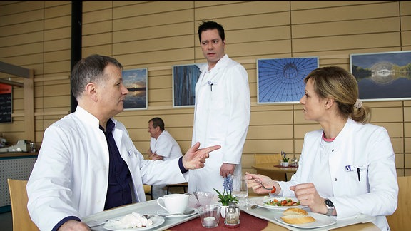 Dr. Philipp Brentano (Thomas Koch, mi.) kommt zufällig vorbei, als Dr. Lea Peters (Anja Nejarri, re.) Dr. Roland Heilmann (Thomas Rühmann, li.) von der Möglichkeit einer dreidimensionalen OP-Planung für eine Leberoperation erzählt. Während Dr. Heilmann das für einen versuch hält, fühlt Philipp sich in seiner Ehre gekratzt. Er ist der behandelnde Arzt des leber-Patienten und verbittet es sich, dass Lea sich ständig einmischt. Sachlich stellt Lea klar, dass es hier nicht um meine und deine geht, sondern darum, einem Patienten das Leben zu retten.