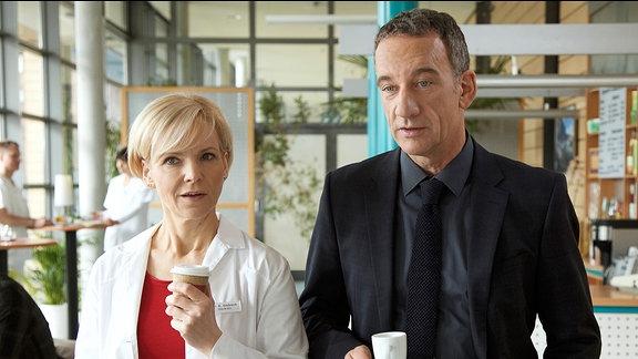 Dr. Kathrin Globisch (Andrea Kathrin Loewig) trifft zufällig Alexander Weber (Heio von Stetten) in der Cafeteria. Alexander würde Kathrin gern zum Abendessen einladen. Sie sagt zwar für den nächsten Abend zu, aber es ist ihr anzumerken, dass sie Alexanders Misstrauen bei der Behandlung seines Sohns immer noch belastet.