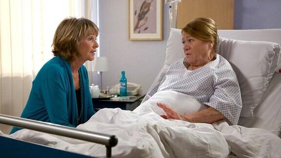 Regina Ströwe (Veronika Nowag-Jones, re.) sitzt im Krankenbett, Barbara Grigoleit (Uta Schorn, li.) sitzt daneben.