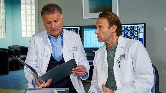 Dr. Martin Stein (Bernhard Bettermann, re.) und Dr. Roland Heilmann (Thomas Rühmann, li.) besprechen eine Krankenakte.