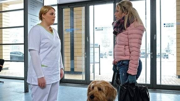 Sina Blasczik (Caroline Maria Frier, re.) kommt mit dem Hund des Fremden in die Sachsenklinik. Er ist in der Innenstadt vor ihr zusammengebrochen und der RTW konnte den Hund nicht mitnehmen. Schwester Miriam (Christina Petersen, li.) verweist sie sofort der Klinik. Hier kann der Hund nicht rein. Sina weiߟ nicht, was sie machen soll. Sie kennt den Besitzer des Hundes nicht und fragt nach den Noteinlieferungen der letzten halben Stunde. Als Miriiam ihr sagt, dass es sich nur um Robert Wünsch handeln könne, versteinert Sinas Gesicht.