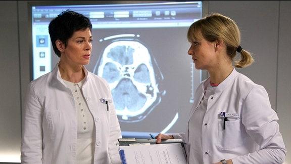 Dr. Elena Eichhorn (Cheryl Shepard, li.) weiß, dass Dr. Lea Peters (Anja Nejarri, re.) die beste Operateurin für Kaminski ist, doch auch sie kann keine Garantie oder ein Versprechen geben, dass Kaminski gerettet werden kann. Die OP ist und bleibt hochriskant.