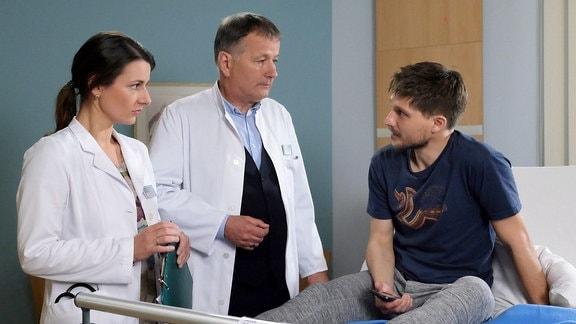 Dr. Roland Heilmann (Thomas Rühmann, mi.) bestätigt Dr. Maria Webers (Annett Renneberg, li.) Diagnose. Die Schrauben in John Neyers' Knie haben sich gelockert und er muss erneut operiert werden