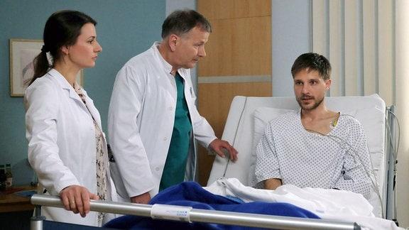 Gemeinsam mit seiner behandelnden Ärztin Dr. Maria Weber (Annett Renneberg, li.) stellt Dr. Roland Heilmann (Thomas Rühmann, mi.) den Ex-Profisportler John Neyers (Rene Erler, re.) zur Rede.