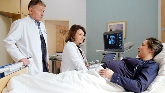 adine Vollmer (Viktoria Gabrysch, re.) ist in der 29. Woche schwanger. Dr. Konstanze Brinkmann (Tamara Rohloff, mi.) und Dr. Roland Heilmann (Thomas Rühmann) mussten ihr Kind in ihrem Bauch operieren. Eigentlich ein Routineeingriff, doch manchmal kann das vorzeitige Wehen auslösen. Das ist nun der Fall. Die beiden Ärzte wollen es erst einmal mit Wehenhemmern versuchen. Nadine hat groߟe Angst ... eigentlich ist es für die Geburt noch viel zu früh.