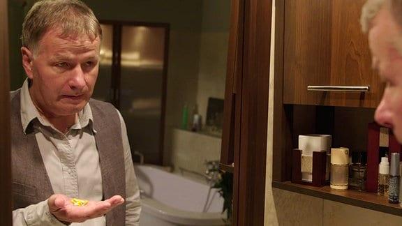 Roland steht mit einer Hand voll Tabletten vor einem Spiegel