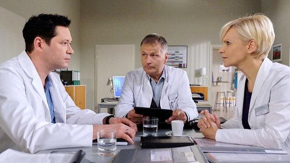 Die Chemotherapie bei Luka Ostberger hat gut angeschlagen, und nun muss der Tumor entfernt werden. Dr. Philipp Brentano (Thomas Koch, li.) plädiert für eine sehr aufwändige OP-Methode. Doch das gefährlich an Lukas Krebs sind Mikrometastasen und um wirklich sicher zu sein, den Krebs vollständig zu entfernen, rät Dr. Roland Heilmann (Thomas Rühmann, mi.) zur Amputation des Unterschenkels. Dr. Kathrin Globisch (Andrea Kathrin Loewig, re.) hört sich beide an, doch am Ende hat der Klinikleiter Heilmann die Entscheidung.